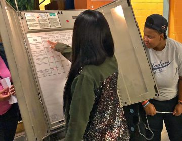 Paul Robeson High School juniors and seniors learn how to use a voting machine. Eligible students were offered a chance to register to vote during their Voter Registration Day event. (Darryl Murphy/WHYY)