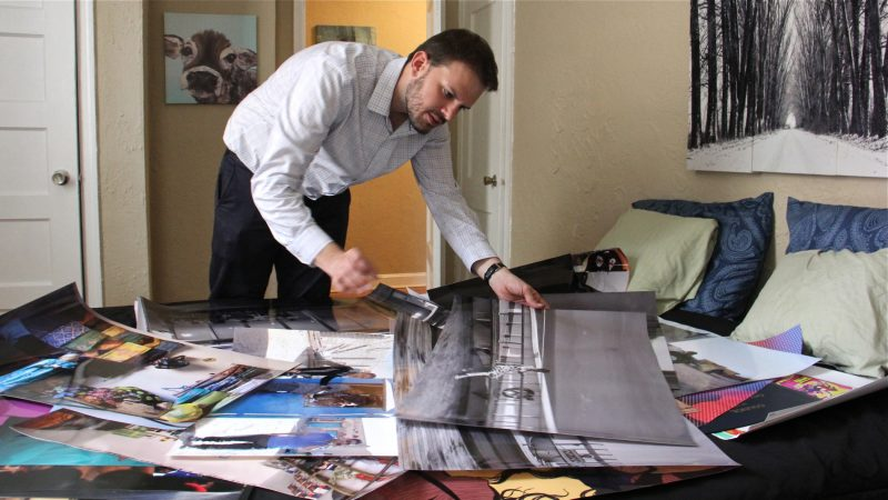 Steve Garguilo lays out photographs taken by Tunisian photographer Sophia Baraket, who died unexpectedly while the exhibit was being planned. (Emma Lee/WHYY)