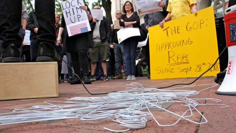 Wire hangers dumped by a protester lie on the ground at the center of a demonstration against Brett Kavanaugh for U.S. Supreme Court. About 200 gathered outside the United States Custom House at 200 Chestnut Street to voice their objections to Kavanaugh's nomination in light of sexual assault allegations. (Emma Lee/WHYY)