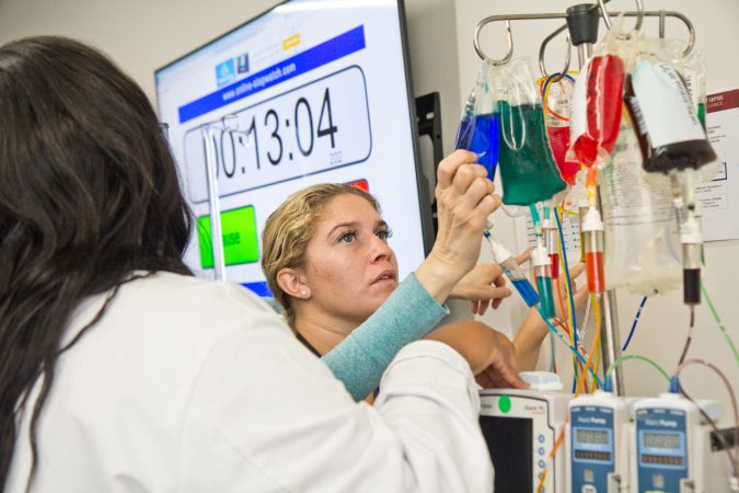 Bianca Marinez, a registered nurse at Penn, examines the IV of a dummy patient at a