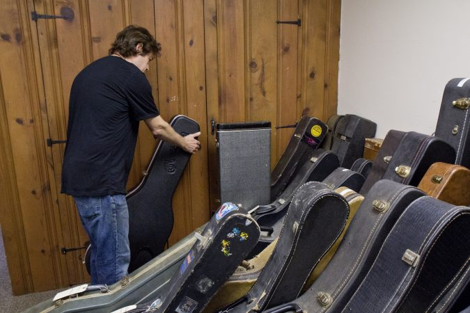 A room filled with customers' instruments is a testament to Tim Huenke's craftsmanship at Superior Guitar Works in Flourtown. (Kimberly Paynter/WHYY)
