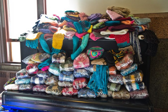 Donated scarves and hats are stacked on top of a piano at the annual Knit In at Philadelphia City Hall. (Kimberly Paynter/WHYY)