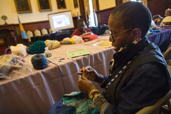 Sakinah Scott is a volunteer with the Knit In and loves to see people coming together for a greater good. Joyce Roby-Washington says her knitting is therapeutic and helps with her dexterity. (Kimberly Paynter/WHYY)