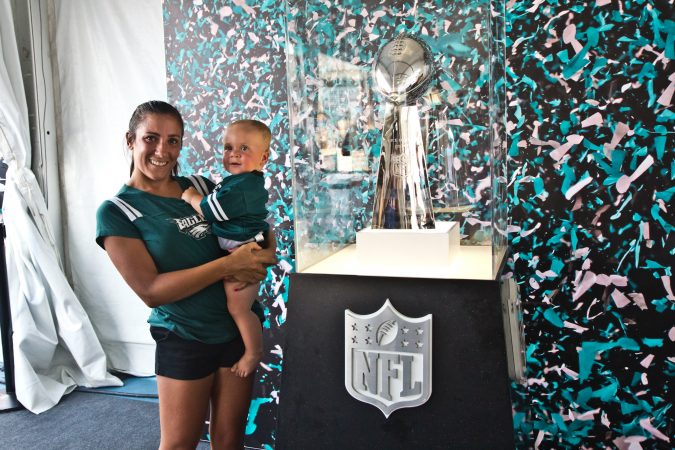 Francesca Tiedeken and her son Matthew Jr., 10 months-old, take a photo with the Lombardi Trophy at a Penn's Landing celebration of the opening of football season. (Kimberly Paynter/WHYY)