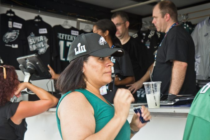 Catherine Johnson, an Eagles fan from Reno, Nevada, tries on her first Eagles hat. (Kimberly Paynter/WHYY)