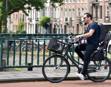 A man talks on the phone while he rides a bike in Amsterdam. Legislation proposed in the Netherlands would impose a fine on bicyclists who use a mobile phone while they're on their bikes. (FaceMePLS/Flickr)