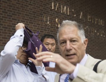 Yu Xue, left, accompanied by her attorney Peter Zeidenberg attempts to block her face with her bag as they exit the federal courthouse in Philadelphia last month. A co-conspirator, Tao Li, pleaded guilty Friday to stealing biopharmaceutical trade secrets from GlaxoSmithKline in what prosecutors said was a scheme to set up companies in China to market them. (AP Photo/Matt Rourke)