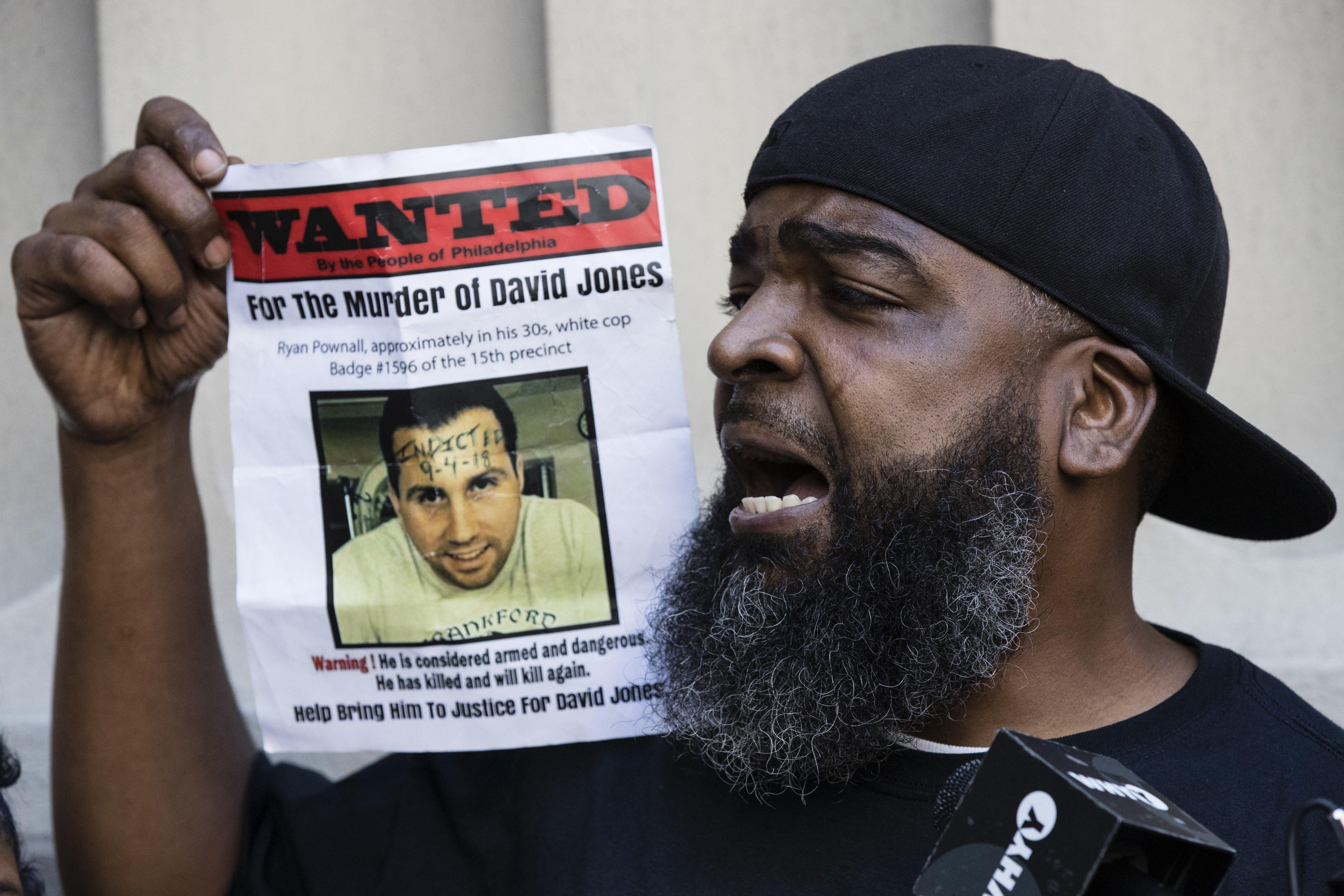 Isaac Gardner speaks while holding up a photo of David Jones
