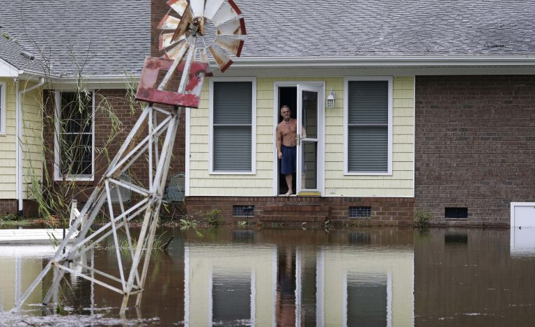 A man peers from his flooded home in Lumberton, N.C., Sunday, Sept. 16, 2018, in the aftermath of Hurricane Florence. (AP Photo/Gerry Broome)