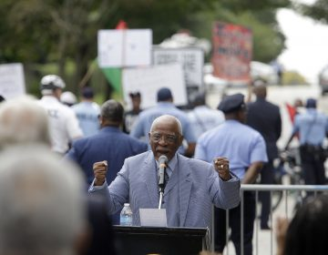 Former Philadelphia Mayor W. Wilson Goode Sr. speaks to supporters, as protesters demonstrate in the background, during a ceremony to celebrate the naming of a street after him Friday in Philadelphia.  (AP Photo/Jacqueline Larma)
