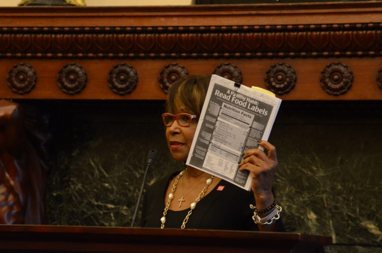 Philadelphia Councilwoman Blondell Reynolds-Brown holds up a test to check for excessive salt in food. A new city law requires restaurants to warn diners of high-sodium menu items. (Tom MacDonald/WHYY)