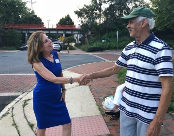 Kathy Jennings, who won Thursday's Democratic primary for attorney general, shakes hands with a voter about 6:30 p.m.  outside Lincoln Towers apartments in Wilmington's Trolley Square neighborhood. (Cris Barrish/WHYY News)
