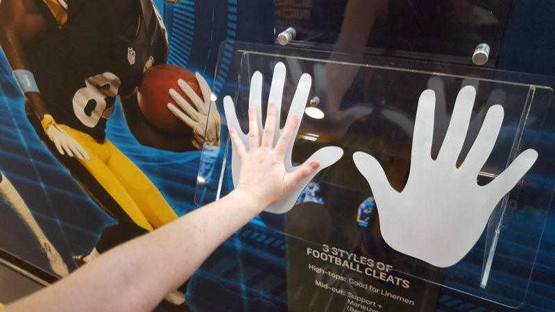 Sara Hoover compares her hand with those of  Dallas Cowboy Dak Prescott. He has the largest hands of any quarterback in the NFL.