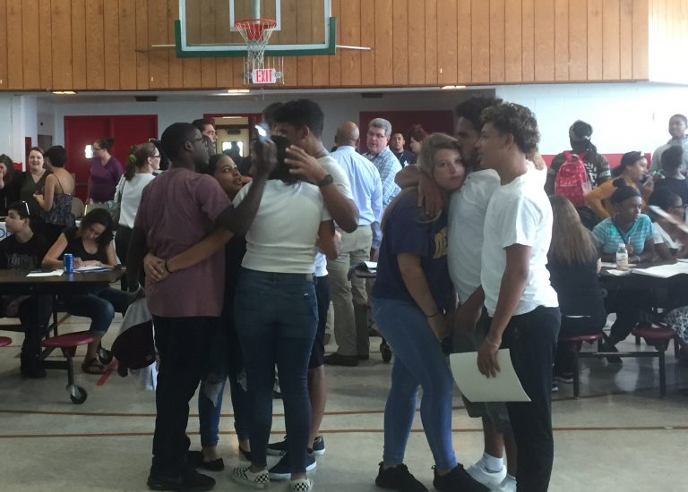 Students embrace a day after learning their charter school is closing. (Zoe Read/WHYY)