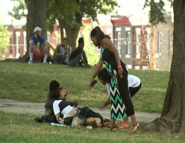 Jasmine Johnson (right), offers Narcan to people using drugs in McPherson Square Park in Kensington. The man refused her offer because he maintained the woman was breathing, and did not want to risk sending her into withdrawal. (Erika Schroeder/WHYY)