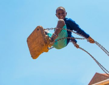 In a work by Kenyan photographer Mwarv Kirubi, a pupil from St. Martin's School Kibagare plays on the swings at break time on 27th January 2017. It is one of 98 works included in