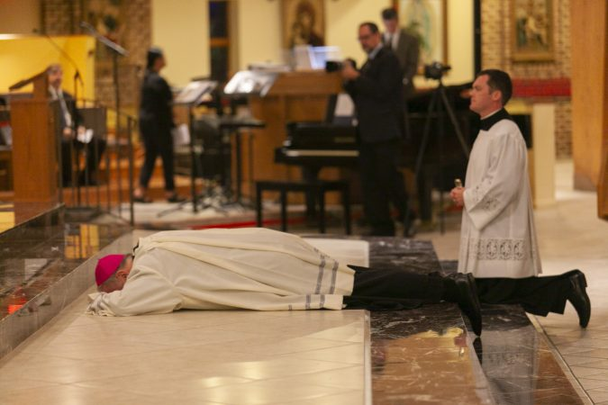 Bishop Dennis Sullivan lying prostrate before the altar, before giving the homily during an evening of prayer for the victims of abuse on September 28, 2018 in Blackwood, New Jersey. (Miguel Martinez  for WHYY)