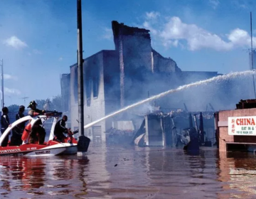 Firefighters battle a fire in flood ravaged Bound Brook, New Jersey during Tropical Storm Floyd in Sept. 1999.
