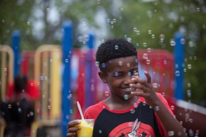 Anthony Payton, 10, of Chester County, plays with bubbles on a playground at Strawberry Mansion Day. (Emily Cohen for WHYY)