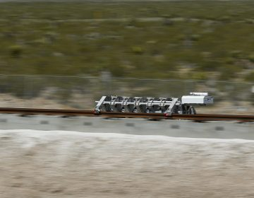 A sled speeds down a track during a test of a Hyperloop One propulsion system, Wednesday, May 11, 2016, in North Las Vegas, Nev. The startup company opened its test site outside of Las Vegas for the first public demonstration of technology for a super-speed, tube based transportation system. (AP Photo/John Locher)
