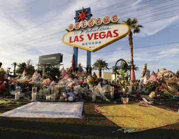 People visit a makeshift memorial for victims of the mass shooting in Las Vegas in October 2017. Fifty-eight crosses were planted in front of the sign to commemorate each of the people killed in the attack. (John Locher/AP)