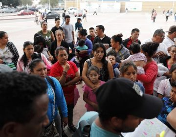 People listen as names are read off a list of who will cross into the United States to begin the process of applying for asylum Thursday, July 26, 2018, near the San Ysidro port of entry in Tijuana, Mexico. As the Trump administration faced a court-imposed deadline Thursday to reunite thousands of children and parents who were forcibly separated at the U.S.-Mexico border, asylum seekers continue to arrive to cities like Tijuana, hoping to plead their cases with U.S. authorities. (AP Photo/Gregory Bull)