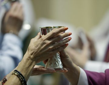 A parishioner celebrates communion at the Cathedral Church of Saint Patrick in Harrisburg, Pa., Friday, Aug. 17, 2018. Since the grant jury report was released last month, the Pennsylvania Attorney General's office has received more than 1,100 calls to it's clergy sex abuse hotline and several other state's attorneys general have initiated their own investigations. (AP Photo/Matt Rourke)