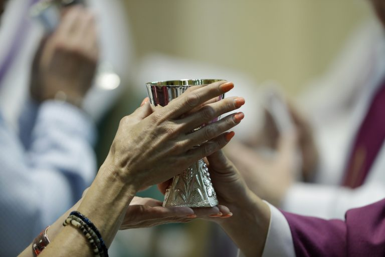 A parishioner celebrates communion at the Cathedral Church of Saint Patrick in Harrisburg, Pa., Friday, Aug. 17, 2018. (Matt Rourke/AP Photo)