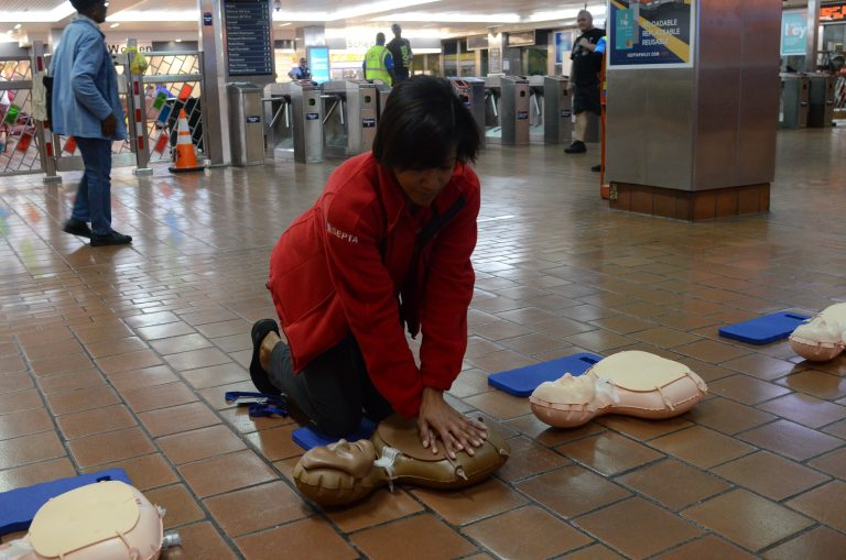 SEPTA Ambassador Carrie Givhan demonstrates CPR on a dummy at Jefferson Station. (Tom MacDonald/WHYY)