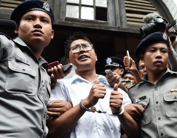 Myanmar journalist Wa Lone (center) is escorted by police after being sentenced by a court to jail in Yangon on Monday. Foreign governments and human rights groups condemned the decision.