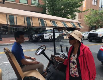 Eunice LaFate quizzes Andrew Cercena about the new golf cart taxi service he's starting for  Buccini/Pollin Group. (Cris Barrish/WHYY)