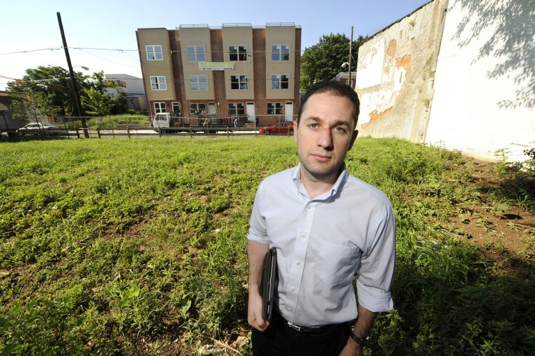 Ori Feibush, owner of ocfrealty in Philadelphia, stands on vacant lots on the 1700 block of Manton St in Point Breeze across the street from four 3-story townhouses his company built and is selling (Clem Murray/Inquirer)