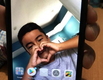 Juan Valiente Velazquez's phone shows a picture of his son, Derickson, who remains in a youth shelter in New York. They were separated by the Border Patrol in Texas in May. Velazquez was deported to Guatemala. Derickson calls his parents three times each week. (John Burnett/NPR_