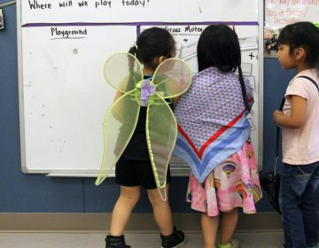 Students play dress-up and draw on a whiteboard in a Christopher House preschool class. (Jackie Mader/The Hechinger Report)