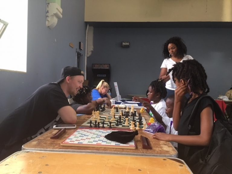 Volunteers teach young kids to play chess at the After School Activities Fair at Francis Myers Reaction Center in Southwest Philly on September 21, 2018. (Taylor Allen/WHYY)