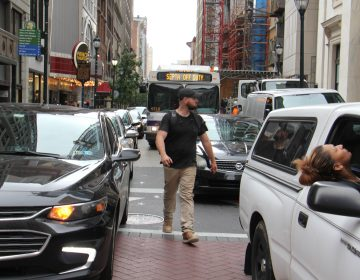 As city officials announce a crackdown on scofflaws who ignore traffic laws, a pedestrian threads his way through lines of cars at Broad and Chestnut streets. (Emma Lee/WHYY)