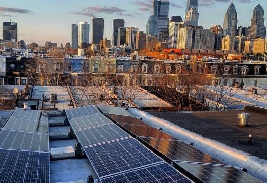 Solar panels and the Philadelphia skyline in winter (Solar States)