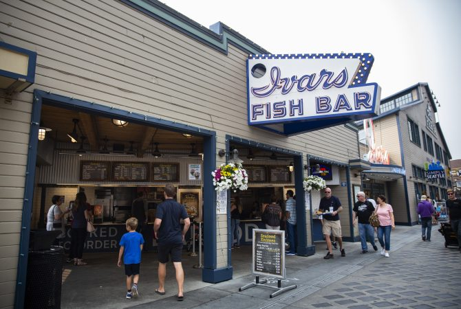 Customers walk up to the Ivar's Fish Bar location, the restaurant's to-go area that's affected by secure scheduling, on the waterfront pier on Wednesday, August 15, 2018 in Seattle, Washington. Ivar's is one of the local businesses affected by Seattle's Secure Scheduling Ordinance, which took effect in July 2017, aiming to establish more predictable work schedules for employees of large retail and food establishments. (Lindsey Wasson for the Inquirer)