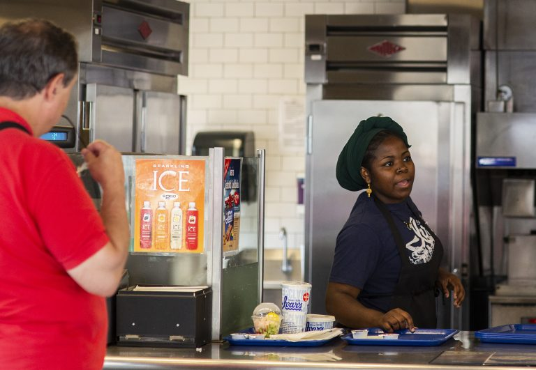 Hawa Hamadi serves up an order at Ivar's Fish Bar, the to-go section of Ivar's on the waterfront pier, on Wednesday, August 15, 2018 in Seattle, Washington. Ivar's is one of the local businesses affected by Seattle's Secure Scheduling Ordinance, which took effect in July 2017, aiming to establish more predictable work schedules for employees of large retail and food establishments. (Lindsey Wasson for the Inquirer)