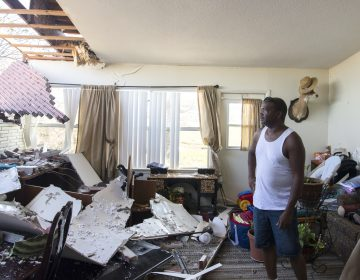 Robert Hill surveys the damage within his living room on Wednesday at Tyndall Air Force Base after Hurricane Michael hit the base last week. Support personnel from Tyndall and other bases were on location to support Airmen returning to their homes to assess damage and collect personal belongings. (Kelly Walker/U.S. Air Force)