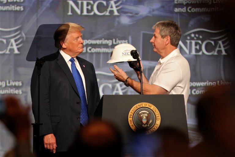 President Donald Trump accepts a hard hat from National Electrical Contractors Association President David Long. Trump closed the NECA convention in Philadelphia with a speech on job creation and training. (Emma Lee/WHYY)