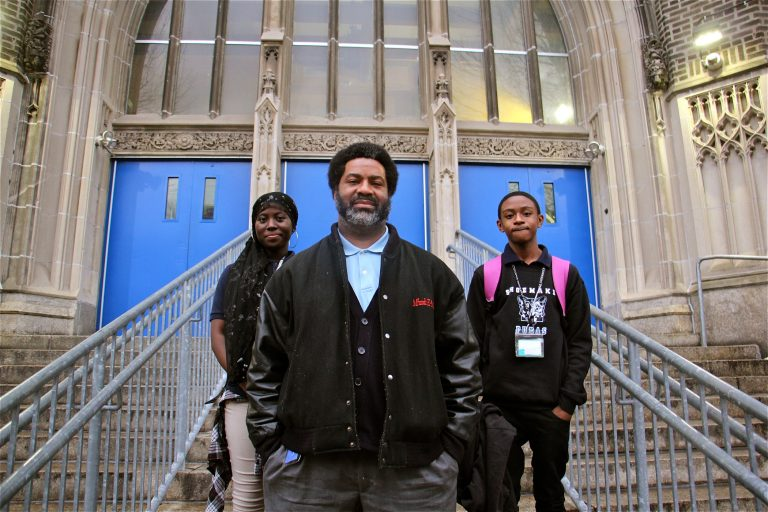 El-Mekki, then principal of Mastery Shoemaker Elementary in Philadelphia, pictured in front of the school with two students in 2018. (Emma Lee/WHYY)