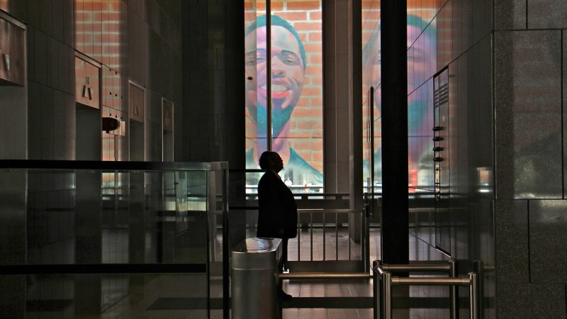 The first floor of the Municipal Services Building is wrapped with the portraits of 17 formerly incarcerated young men and women as part of the Mural Arts