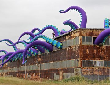 Giant purple green and blue tentacles protrude from the windows of a dilapidated warehouse at the navy yard