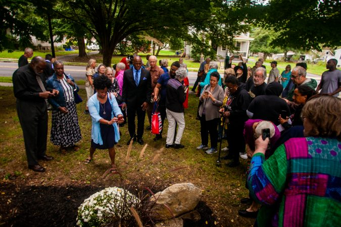 Attendees gather around a memorial stone during a service for the forgotten slaves buried on the grounds of Middletown Friends Meeting at Langhorne, Pa. on Saturday, Oct. 6, 2018. (Brad Larrison for WHYY)