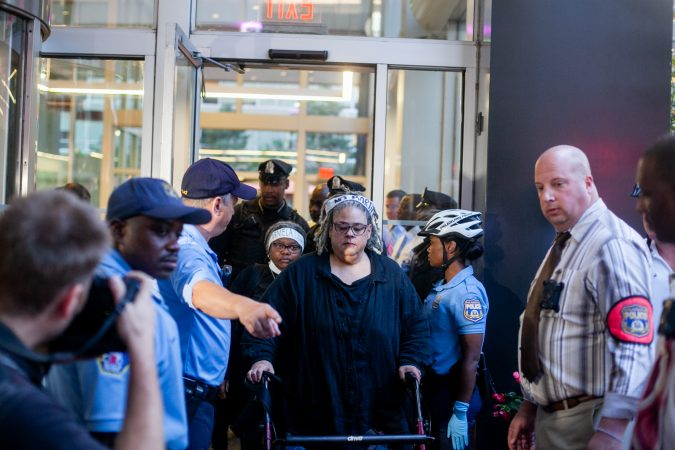 Clergy members Dr. Wende Marshall and the Rev. Renee McKenzie leave the lobby of 2000 Market Street after blocking an entrance and facing arrest. (Brad Larrison for WHYY)
