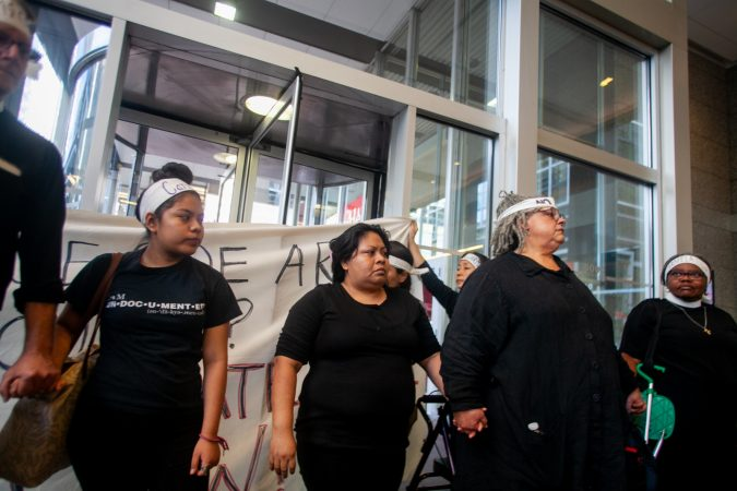 Undocumented immigrant Carmela Apolonio Hernandez (center) and her daughter Keyri Artillero Apolonio block an entrance with clergy in to the lobby of 2000 Market Street Wednesday after demanding a meeting with U.S. Sen. Bob Casey at his office. (Brad Larrison for WHYY)