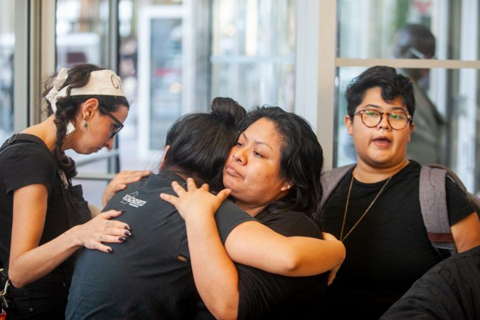 Undocumented immigrant Carmela Apolonio Hernandez hugs her daughter Keyri Artillero Apolonio while blocking  an entrance with Philadelphia clergy in to the lobby of 2000 Market Street Wednesday after demanding a meeting with U.S. Sen. Bob Casey at his office. (Brad Larrison for WHYY)