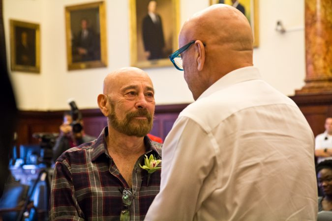 Charles Massucci stares into the eyes of his partner of 47 years, Joseph DiDio, as they renew their vows at the National Coming Out Day event at City Hall Thursday. (Kimberly Paynter/WHYY)