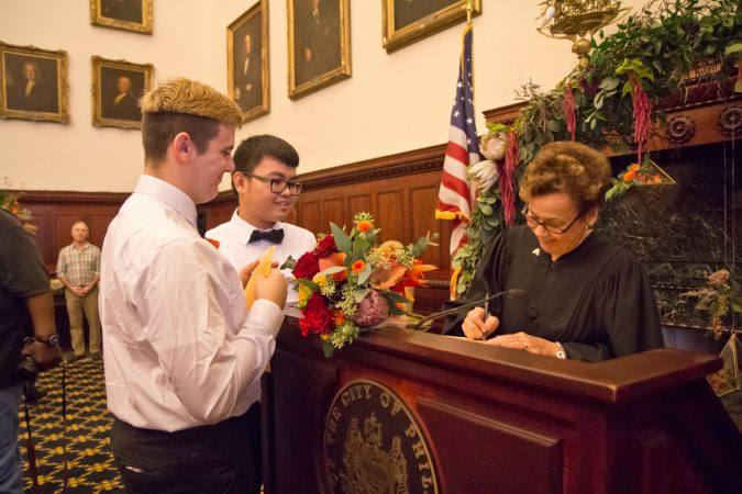 Honorable AnnM.Butchartsigns the marriage certificate at Romeo Lopaz and Hok Nhi at the National Coming Out Day event at City Hall Thursday. (Kimberly Paynter/WHYY)